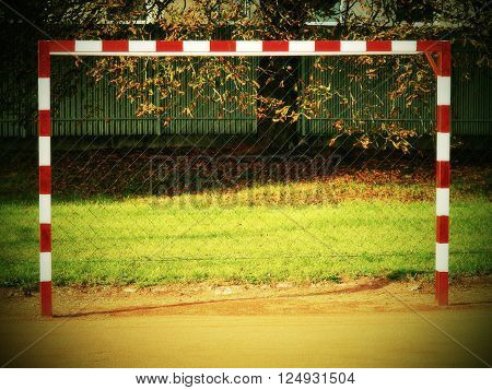 Empty gate. Outdoor football or handball playground, dry red crushed bricks surface on ground