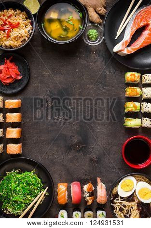 Sushi and japanese food on dark background. Sushi rolls hiyashi wakame miso soup ramen fried rice with vegetables nigiri salmon steak soy sauce ?hopsticks. Asian/Japanese food frame. Overhead