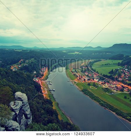 Early autumn morning on rocks above big river, fresh blue cloud in the sky, lights in town on river banks. Green forests in landscape, daybreak at horizon