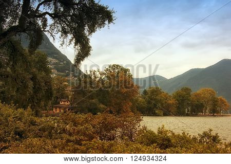 View on Lugano lake. In foreground are trees and bushes. In the middle can be seen lake and pretty haus. Mountains and sky in back plane.