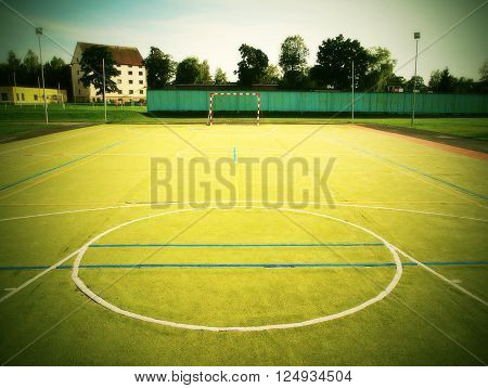 Empty outdoor handball playground, plastic light green surface on ground and white blue bounds lines.