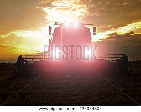 Abandoned Combine Harvest Wheat With Lighted Main Lights In The Middle Of A Farm Field. Morning Yell
