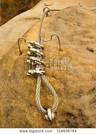 Iron Twisted Rope Fixed In Block By Screws Snap Hooks. Detail Of Rope End Anchored Into Sandstone Ro