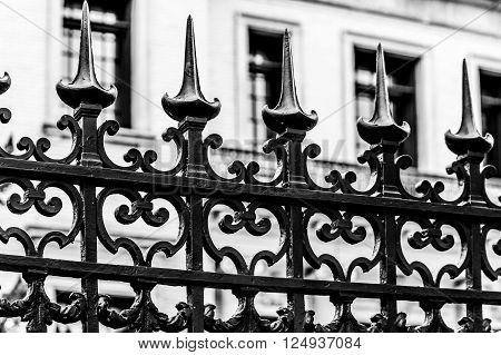 An ornate black iron fence by a white building
