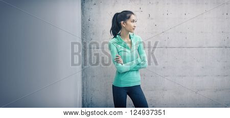 Athletic young woman standing arm folded looking to her side