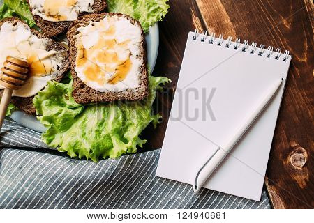Sandwich with mascarpone cheese, honey and salad next to notebook on wooden background