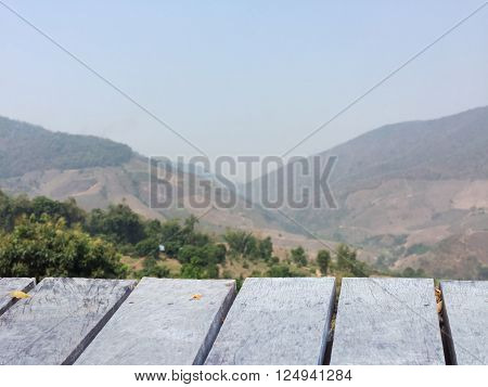 wooden table perspective with blurred deforested mountain and sky background