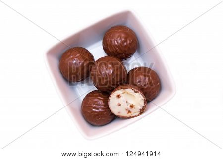 Chocolate pralines on a square bowl on a white background seen from above