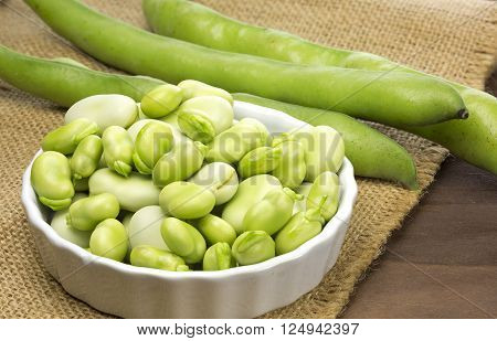 Fresh broad beans in a ceramic pot on wooden background