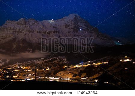 View of Eiger north face Alps Switzerland on clear starry night. Eiger Nordwand mountain in Swiss Bernese Alps. Mountains and snowy village in winter time with Christmas lights. Blue sky with stars.