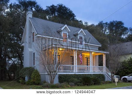 Two story house lit up at twilight