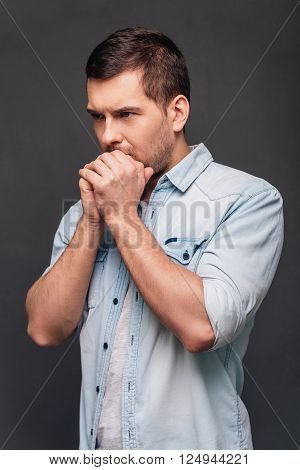 Just a moment to overthink everything. Side view of handsome young man keeping hands clasped and looking thoughtful while standing against grey background