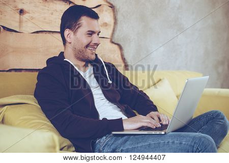 Surfing net at home. Cheerful young man using his laptop with smile while sitting on couch at home