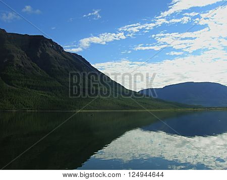 Reflection of mountains and blue sky with clouds in the water floating boat at the foot of the mountain