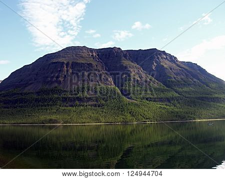 Landscape mirroring mountains in stagnant water surface