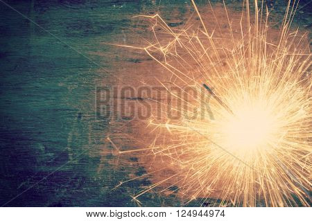 The sparkler on the old wooden background retro effect image