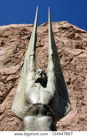 Winged Sculpture statue with rock and blue sky in the background at Hoover Dam