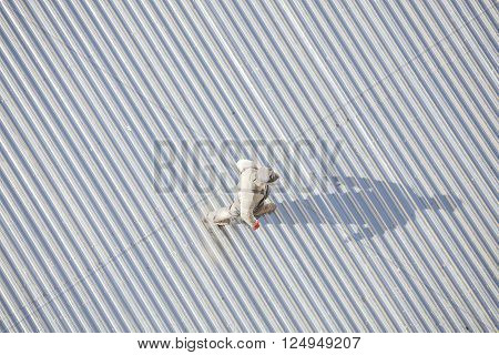 Szczecin, Poland - April 07, 2016: Man Inspecting A Roof Made Of Corrugated Metal Sheets After Repai