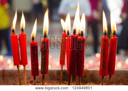 Burning red candle at chinese shrine for making merit in chinese