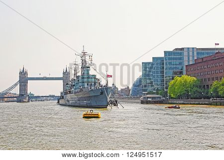 Belfast Ship and Tower Bridge over River Thames in London UK. Tower Bridge crosses the Thames River and is an iconic symbol for London. Belfast is currently a museum ship.