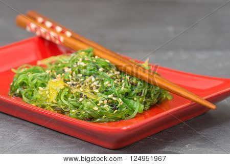 plate of delicious seaweed salad on a red plate with chopsticks.