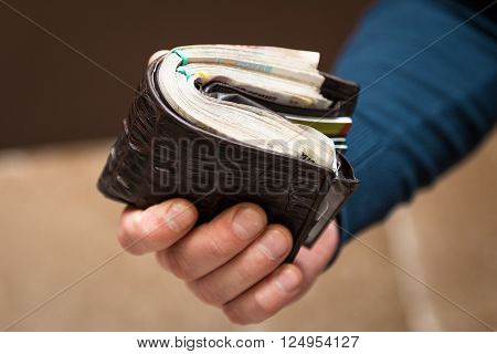 A man holds a purse with money