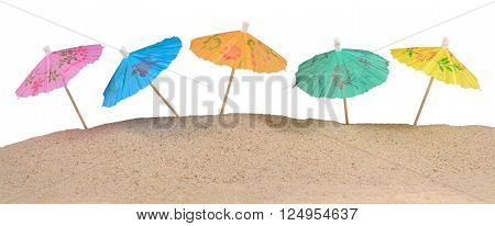 Cocktail Umbrellas In Sand On A White