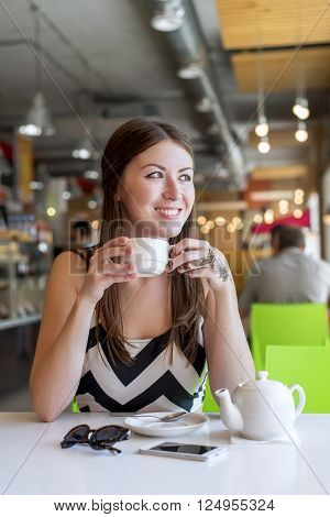 Beautiful girl in a cafe drinking tea, coffee, breakfast in the restaurant looking out into the street, a business woman on the desk phone maker glasses, brunette Happy smiling, relaxing in the room