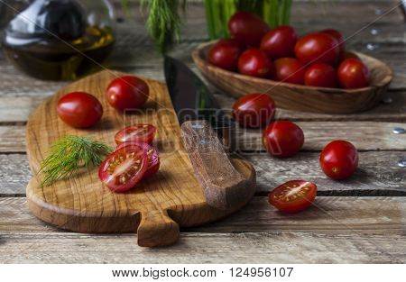 fresh juicy and tasty cherry tomatoes and dill on cutting board