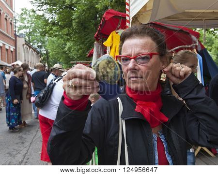 TURKU, ABO FINLAND IN JUNE 29. Closeup view of a customer at the Medieval Market Festival on June 29, 2013 in Turku, Abo Finland. Unidentified lady looks for eardrops in a mirror.