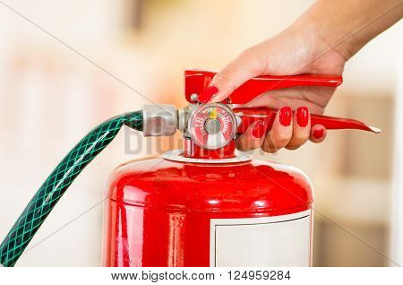 Closeup woman hands with red nailpolish showing how to operate fire extinguisher.