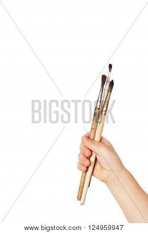 Paint brushes in a child hand isolated on white background. The concept of education drawing children's art fresh creative ideas etc.