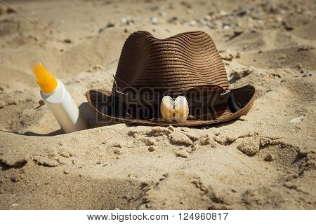 Shells and sunglasses on a hat and a bottle of sunscreen lotion lying on the sand. Vacation theme. Toned effect