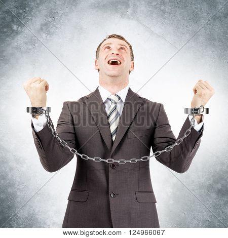 Happy businessman in cuffs on grey wall background