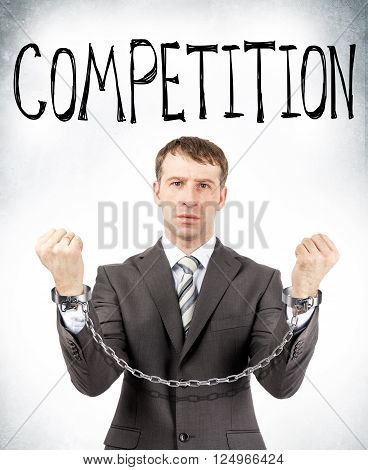 Businessman in cuffs with competition word on grey wall background