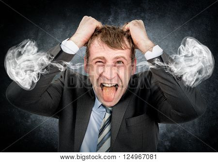 Businessman tearing his hair and with smoke from his ears on grey wall background
