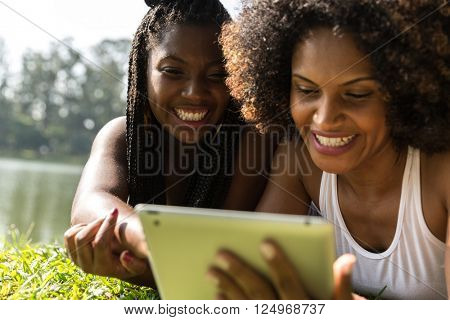 Brazilian women using tablet computer in the park