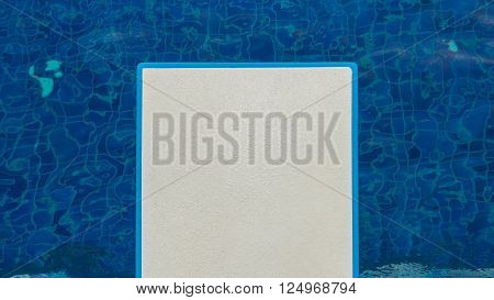 a white diving board with blue water background
