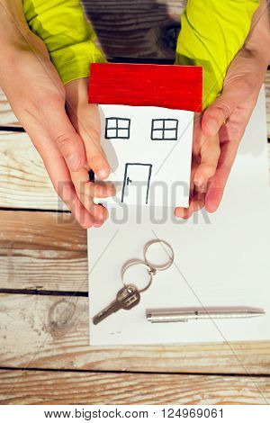 Real estate and family home concept - hands holding paper house