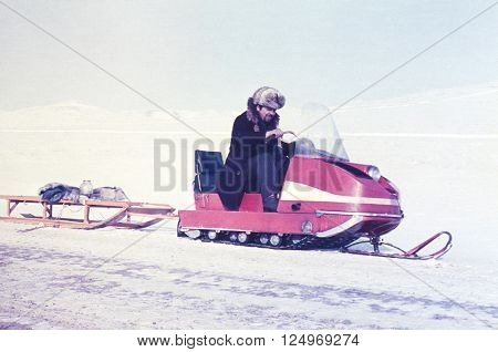 CHUKCHI PENINSULA, USSR - APRIL 15,1979: Soviet gold-prospector transports on a snowmobile glass jar with machine oil in Chukchi Peninsula, USSR at April 15,1979