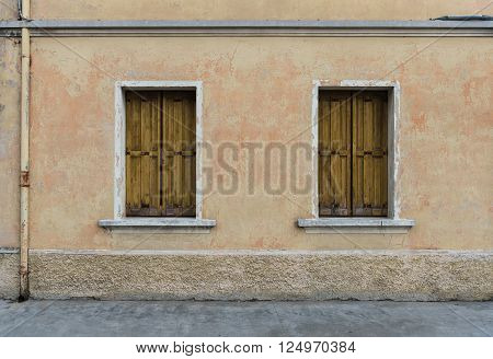 Two old windows with yellow shutters closed in the old scratched wall, Palmanova, Italy