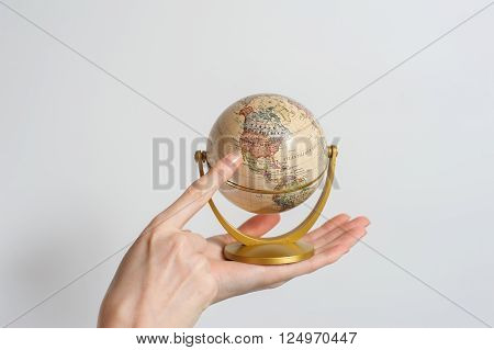 Female with small desktop globe of planet earth in hand. Forefinger pointing to North America. White background.