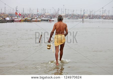 ALLAHABAD, INDIA - FEBRUARY 7, 2013: Hindu devotee (sadhu) is coming to confluence of Ganges and Yamuna River for ritual bathing during the festival Kumbh Mela. The world's largest religious gathering