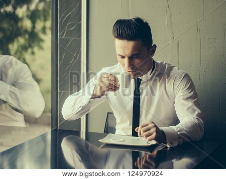 Man young handsome elegant model wears white shirt black skinny necktie sits at table drinks coffee reflects in glass window and looks in cup indoor on grey background