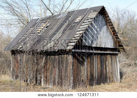 Old abandoned wooden shed with leaky roof