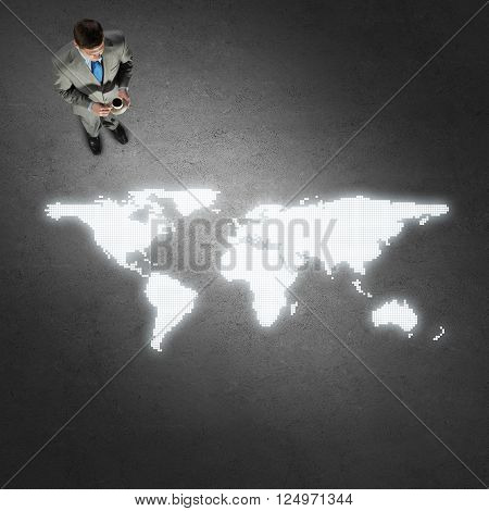 Top view of thoughtful businessman looking at glowing world map on concrete floor