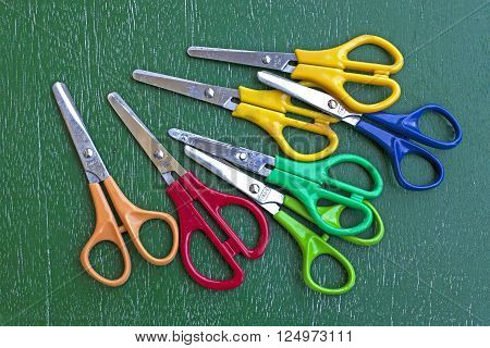 many scissors on green wooden table background