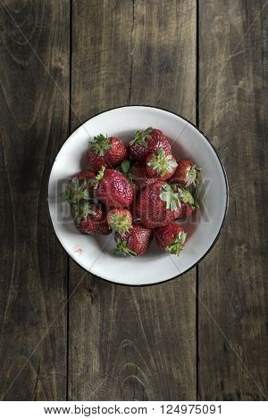 Strawberry in a bowl on wooden table top view