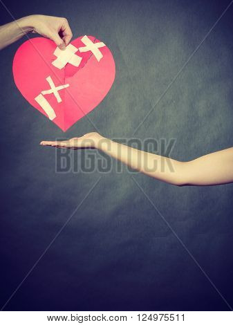 Broken heart difficult love concept. Couple woman and man hands holding paper red heart fixed with plaster bandage. Rift in relations.