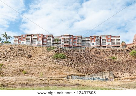 PORT ELIZABETH SOUTH AFRICA - FEBRUARY 27 2016: A block of flats on a hill overlooking the central parts of Port Elizabeth. Street art is visible below